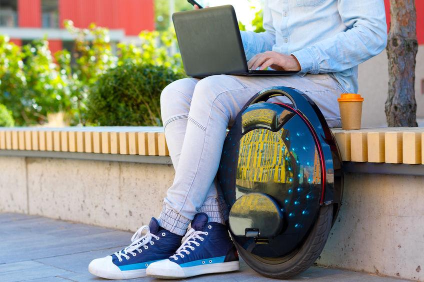 homem sentando em local ao ar livre trabalhando com um notebook, ao lado dele tem um monociclo