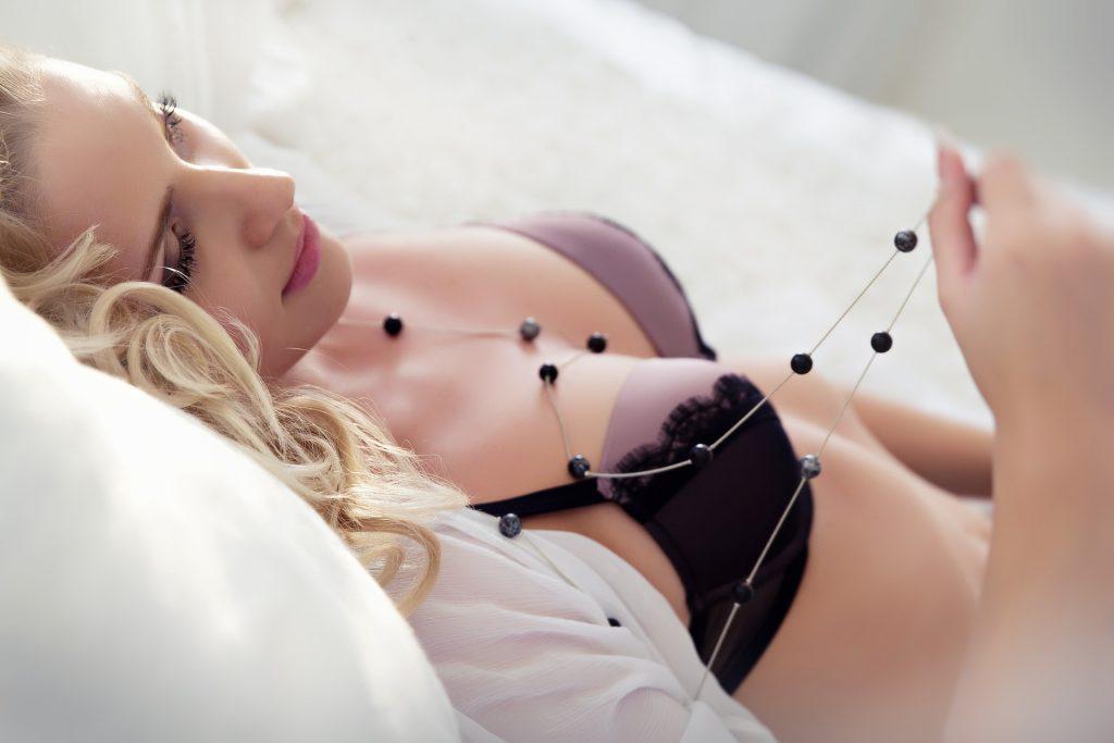 Imagem de mulher sensual deitada na cama brincando com colar