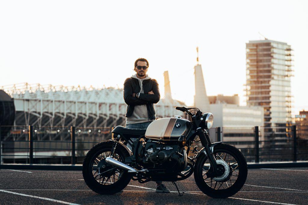 Homem em pé atrás de moto.