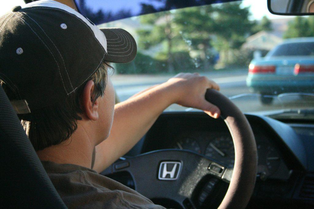 Um homem visto de costas segurando o volante do carro