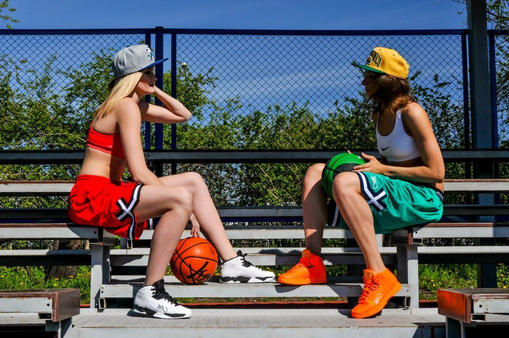 Duas jogadoras de basquete sentadas em arquibancada ao ar livre.