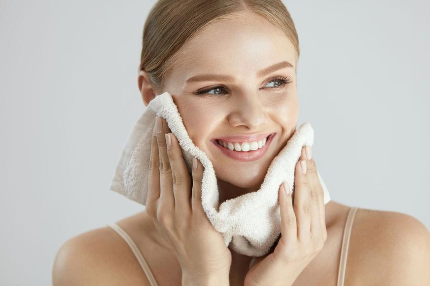 Moça sorri enquanto seca a face com toalha de rosto