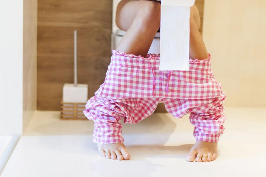 Uma mulher de pijama quadriculado rosa sentada em um vaso sanitário segurando rolo de papel higiênico na mão