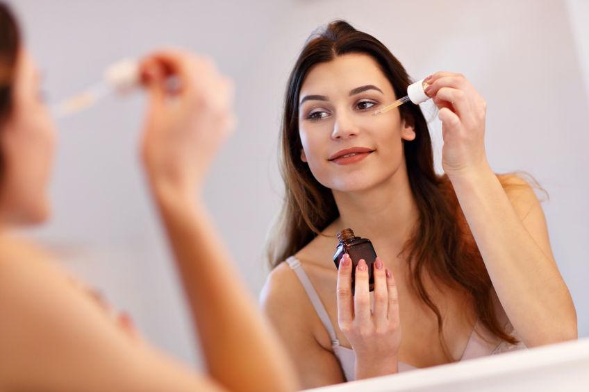Imagem de uma mulher aplicando um sérum no rosto.