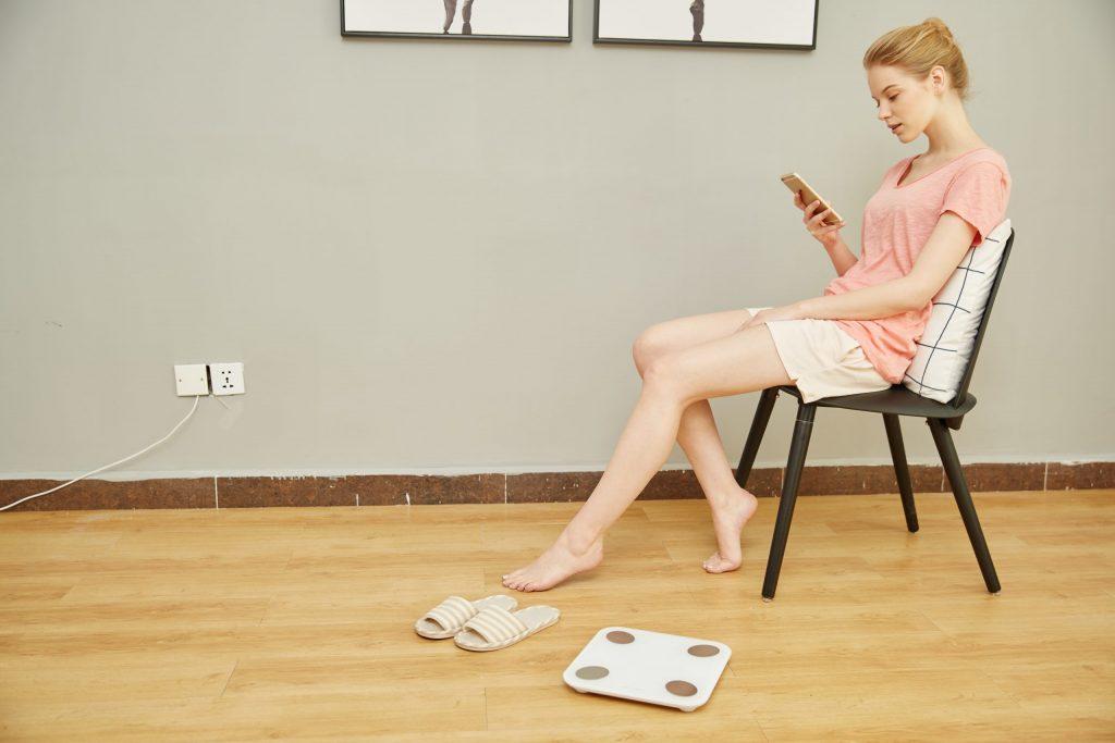 Imagem de uma mulher sentado ao lado de uma balança.