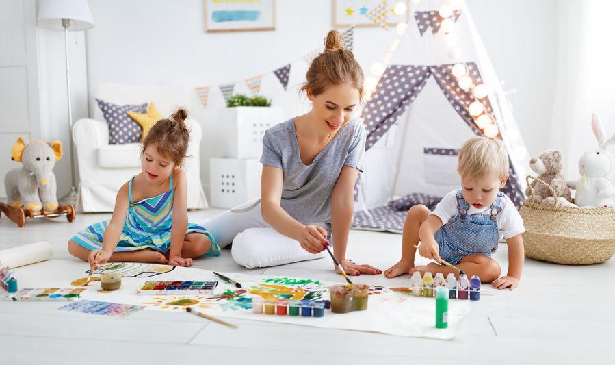 Imagem mostra uma mãe brincando com seus filhos dentro de casa. Eles usam pinceis e tintas para pintar papéis espalhados pelo chão, com uma barraca infantil montada ao fundo.