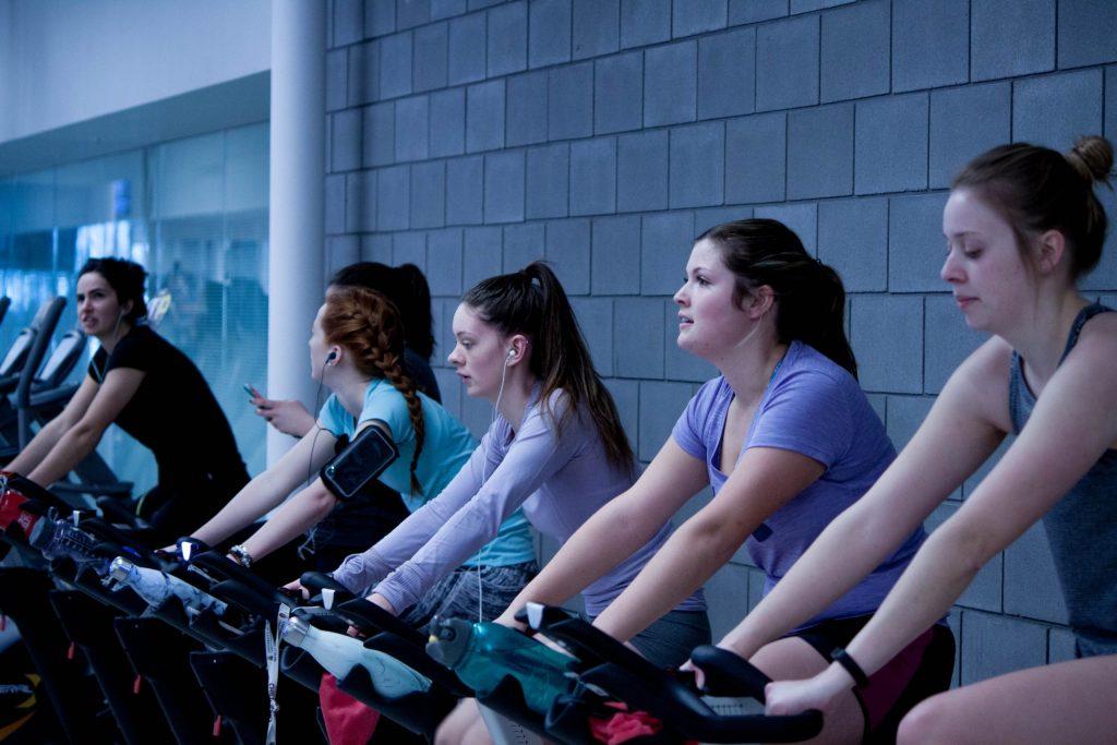Imagem mostra uma fileira de mulheres pedalando em bicicletas ergométricas numa academia.
