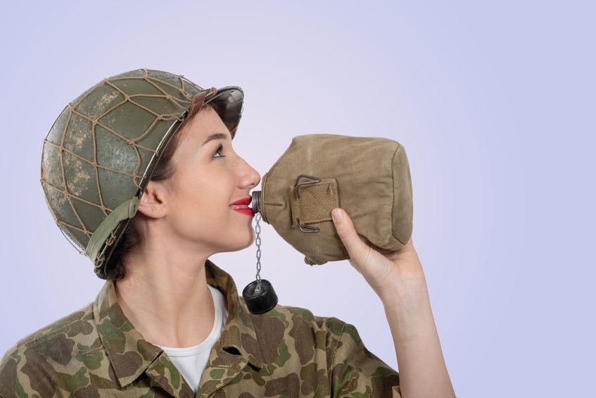 Imagem mostra uma mulher com roupas militares bebendo de um cantil.