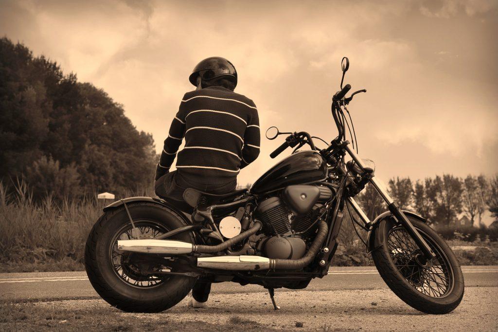 Imagem mostra uma pessoa sentada sobre sua moto usando um capacete.