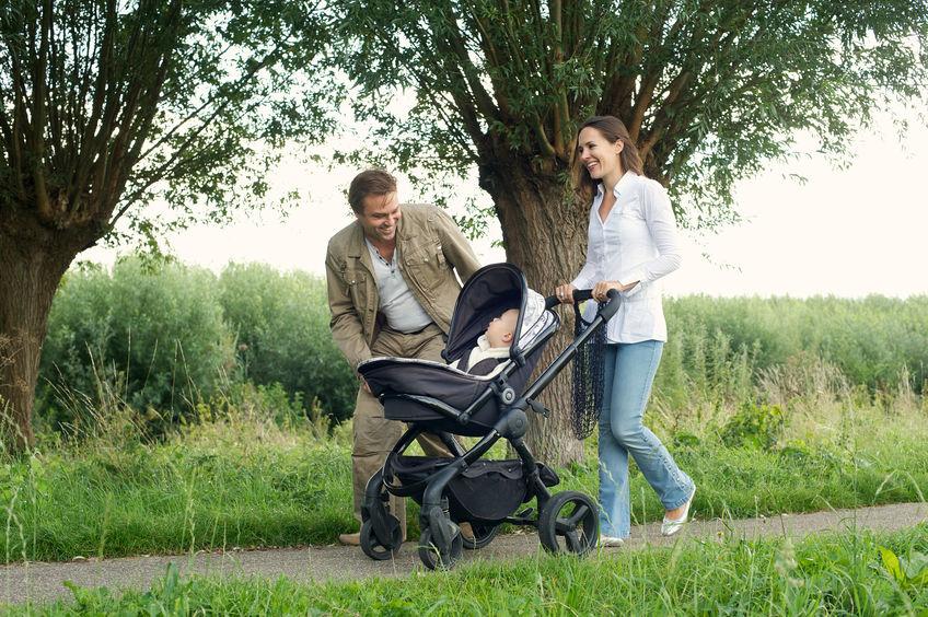 Pai e mãe passeando com bebê em carrinho de bebê no parque.