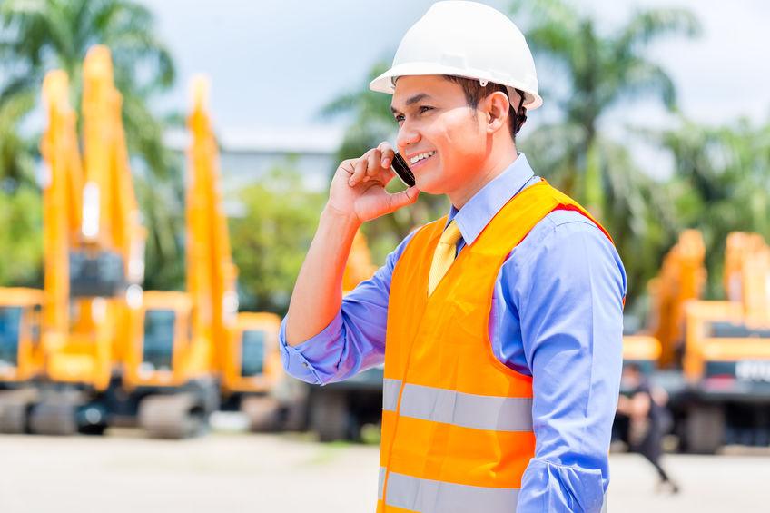 Imagem de um empreiteiro falando ao celular.