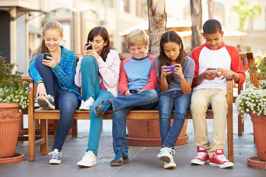 Imagem de um grupo de crianças usando celulares.