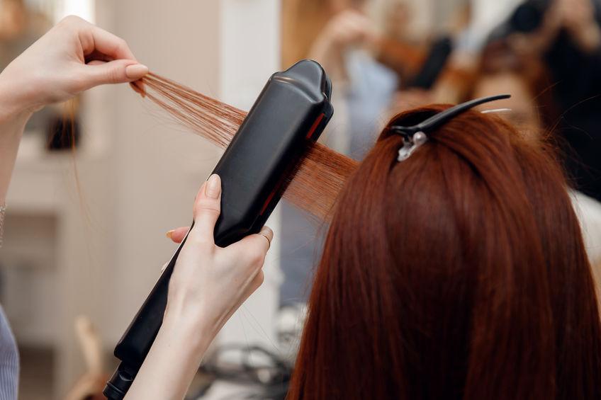 Na foto uma cabeleireira fazendo chapinha no cabelo de uma mulher.