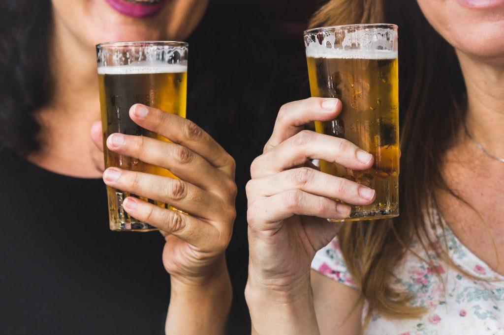 Imagem mostra, em foco seletivo, dois copos de vidro cheios de cerveja, com marcas de gole, segurados por duas mulheres, em segundo plano no quadro.