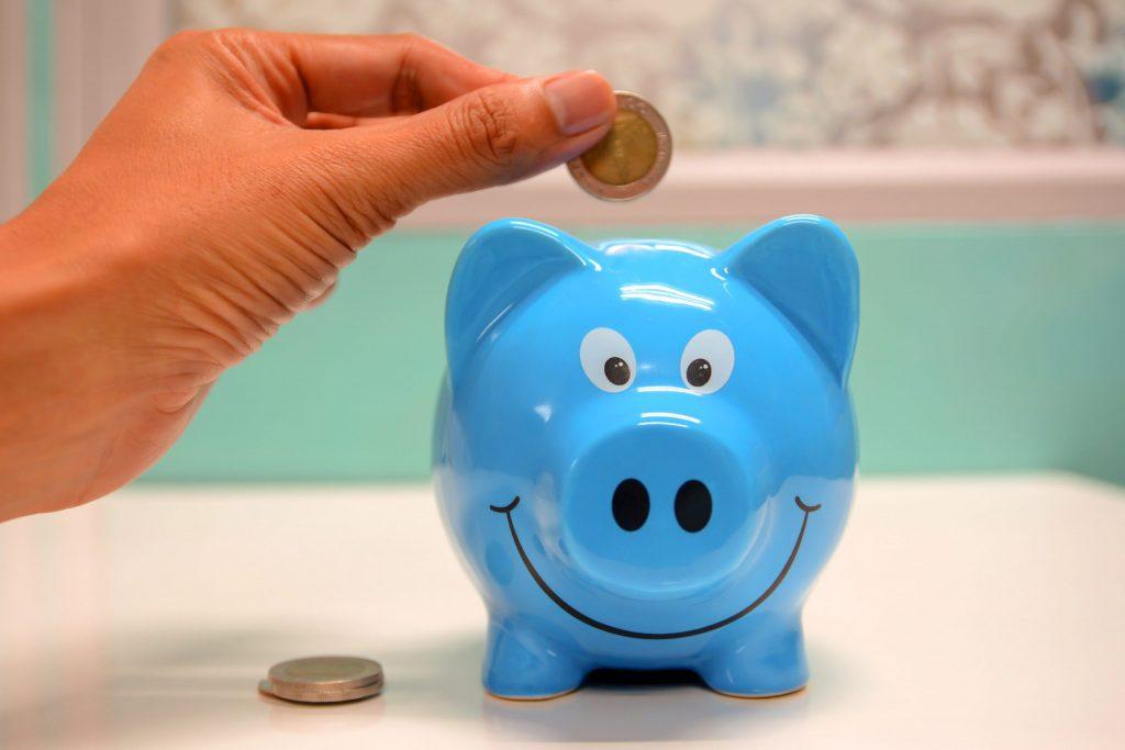 Mão colocando moeda em um cofre azul em forma de porquinho.
