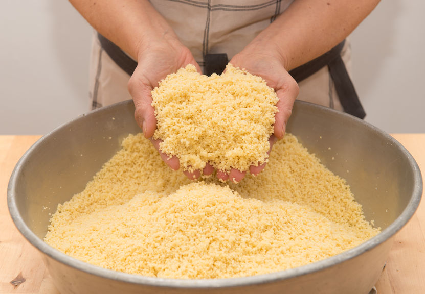 Mãos de pessoa preparando massa de cuscuz em bacia