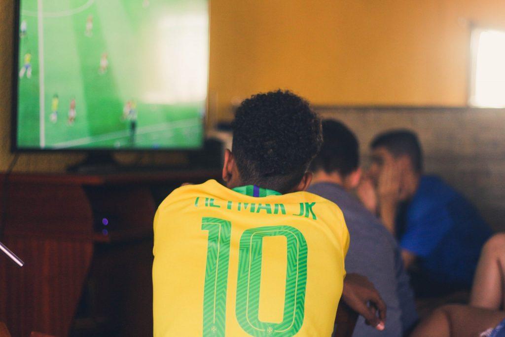 Imagem mostra um homem assistindo a um jogo da seleção brasileira em uma televisão.