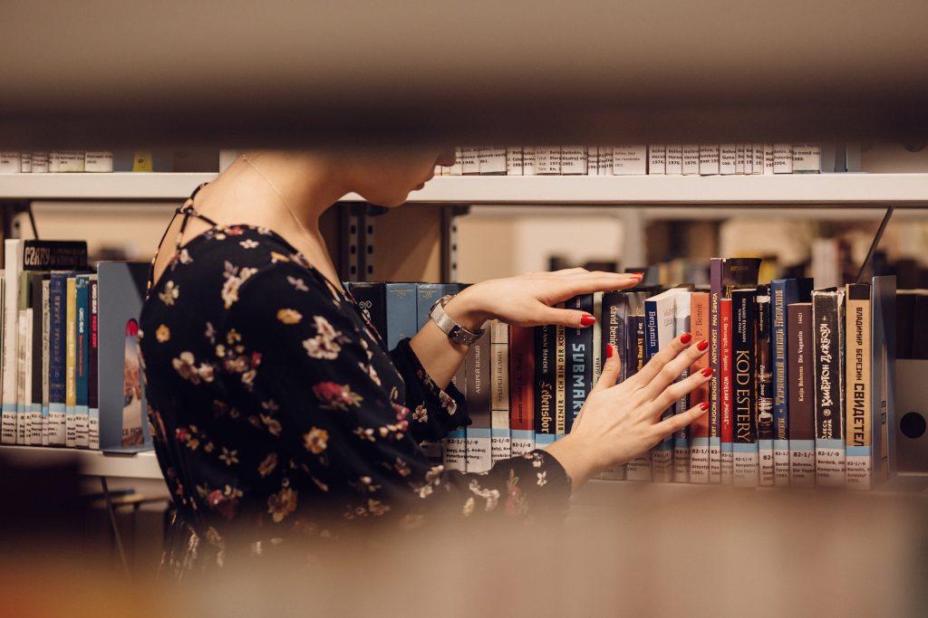 Na foto uma mulher escolhendo um livro em uma estante.