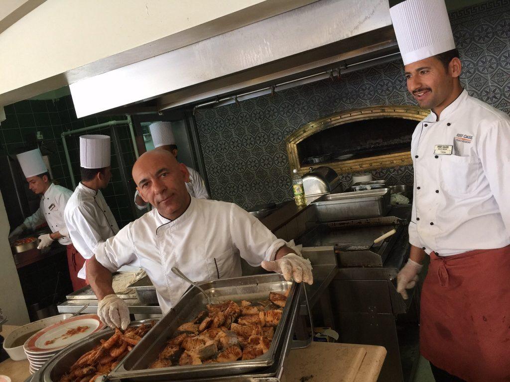 Imagem mostra cozinheiros trabalhando em uma cozinha profissional.