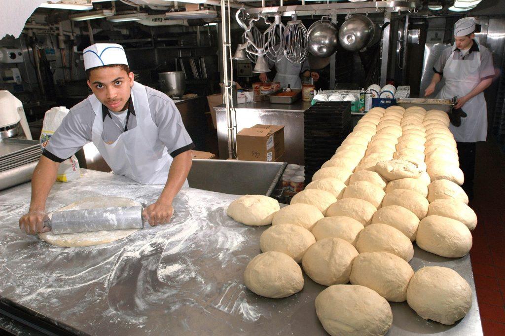 Imagem mostra um homem abrindo uma massa de pão em uma cozinha profissional.