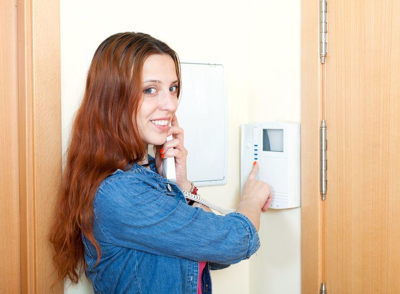 Imagem mostra uma mulher sorrindo enquanto usa um vídeo porteiro.