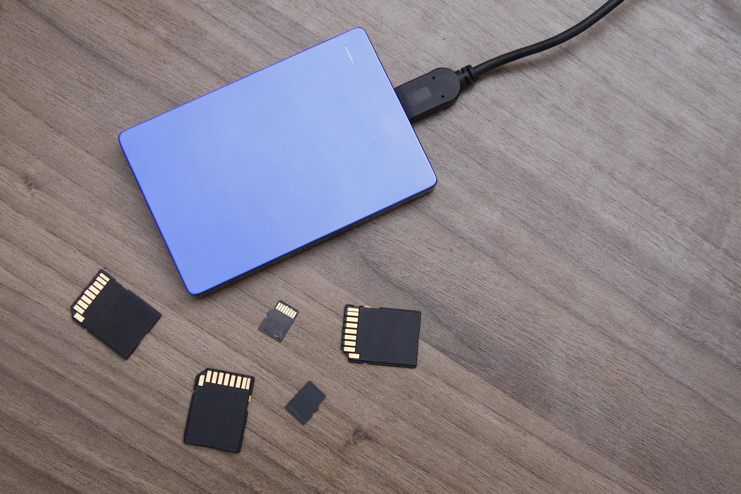 Imagem de HD externo azul junto de vários cartões de memória
