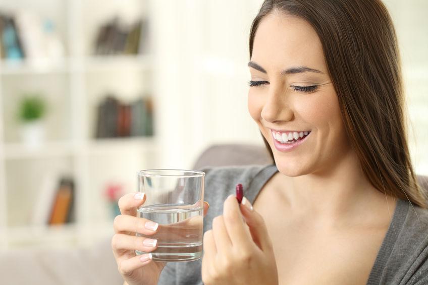 Imagem de uma mulher tomando uma pílula de licopeno.