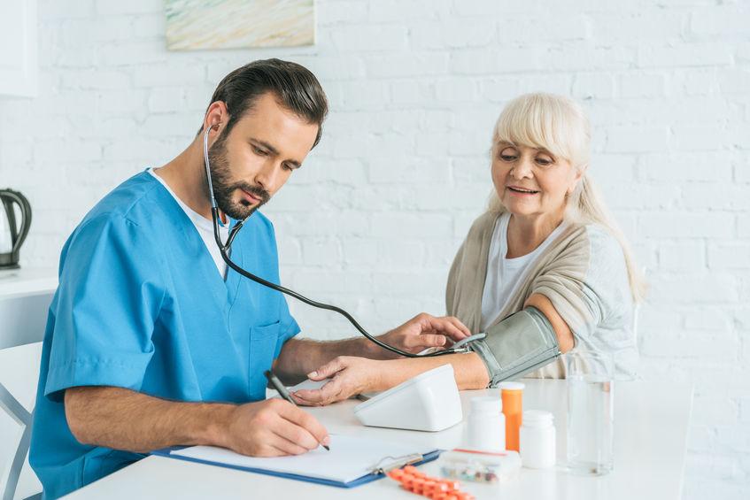 Na foto um médico aferindo a pressão de uma mulher.