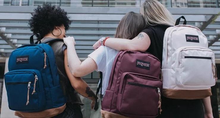 Imagem de três jovens usando mochilas Jansport.