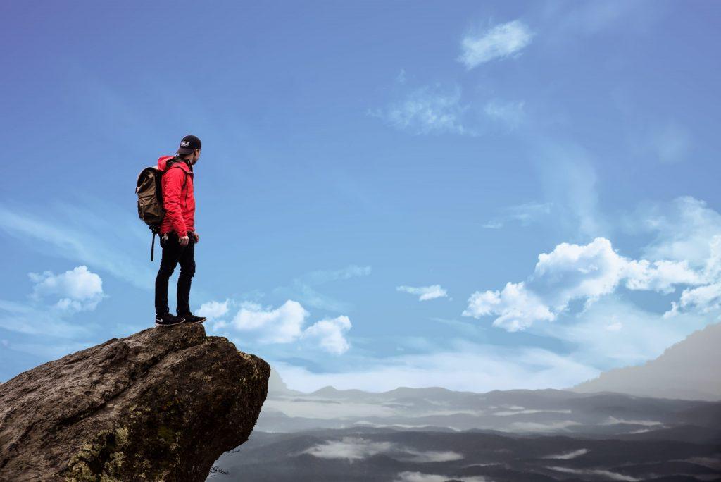 Imagem mostra um homem, que usa uma mochila cargueira, em cima de uma pedra, observando o horizonte, de um ponto bastante alto.