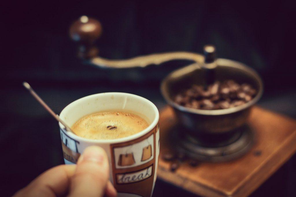 Imagem de pessoa segurando uma caneca de café com um moedor manual ao fundo