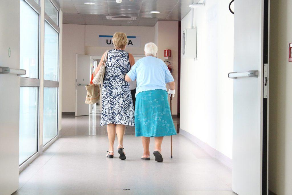 Mulher andando de braço dado com senhora no corredor de hospital.