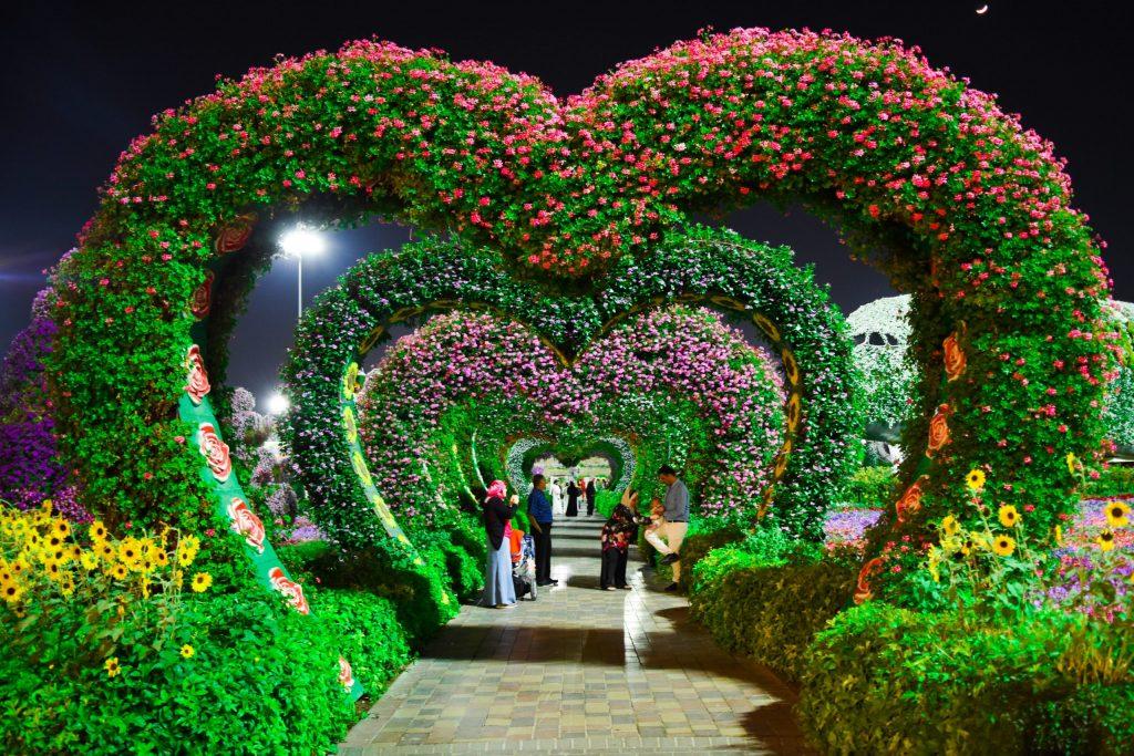 Imagem mostra um jardim iluminado à noite com diversas pessoas em pé.