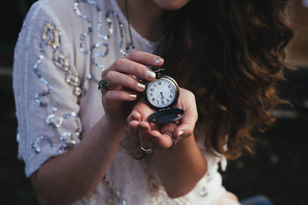 Na foto uma mulher segurando um relógio de bolso nas mãos.