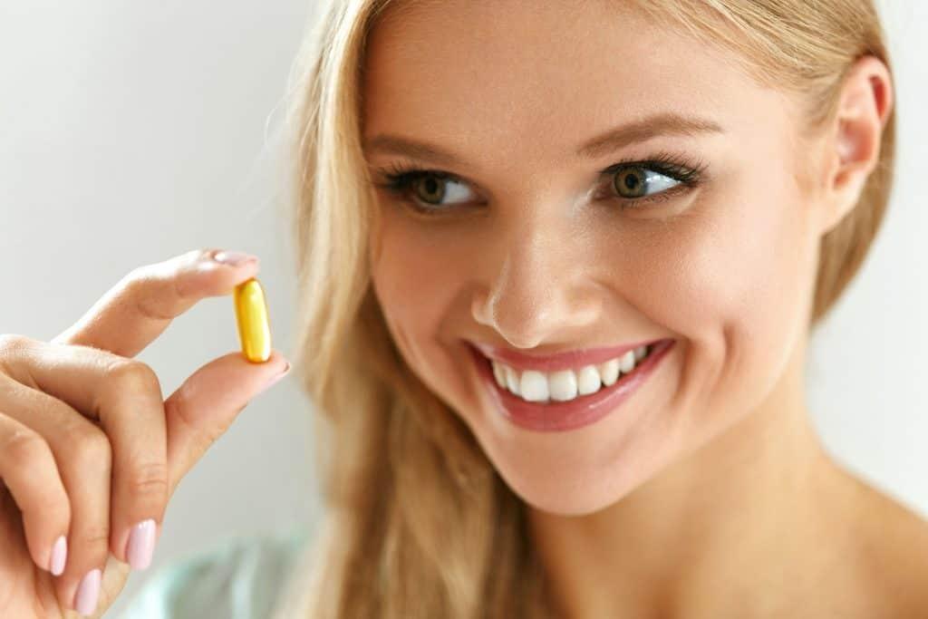 Mulher segurando um comprimido.