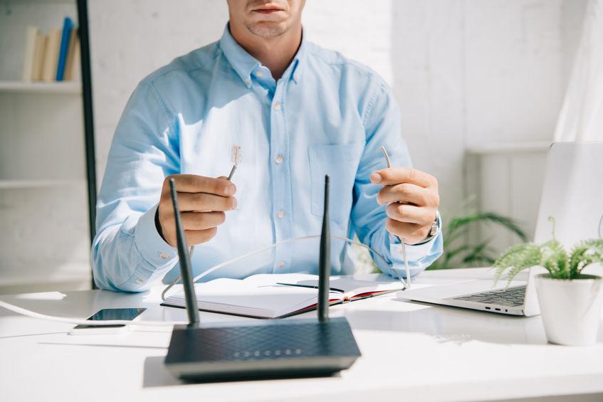 Imagem mostra um homem sentado a uma mesa em frente a um roteador.