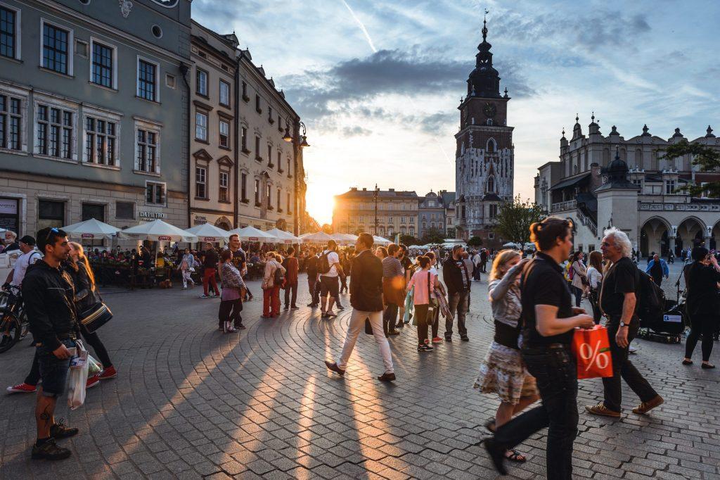 Pessoas andando em praça central de Cracóvia, na Polônia.