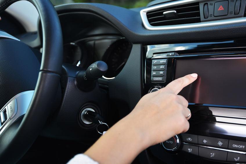 Imagem mostra um homem dirigindo um carro com um sistema de som instalado no painel. Um celular também se apoia no painel, por meio de um suporte.
