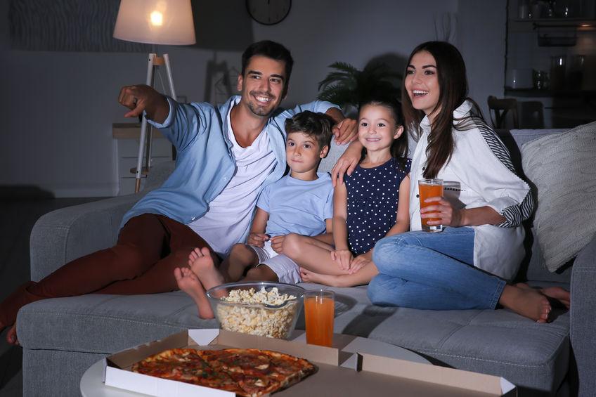 Pai, mãe e dois filhos sentados no sofá comendo pipoca e vendo TV.