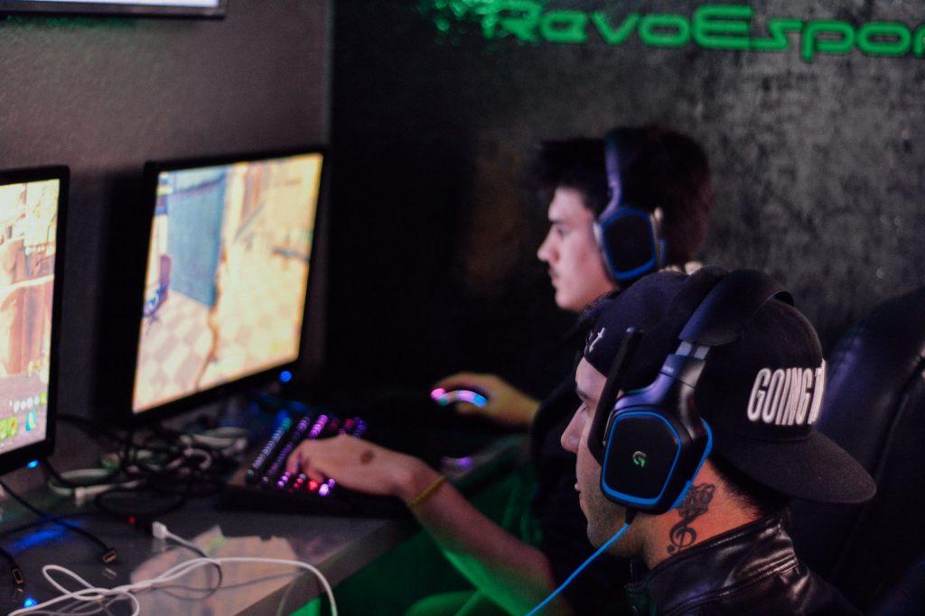 Imagem de duas pessoas jogando em computadores
