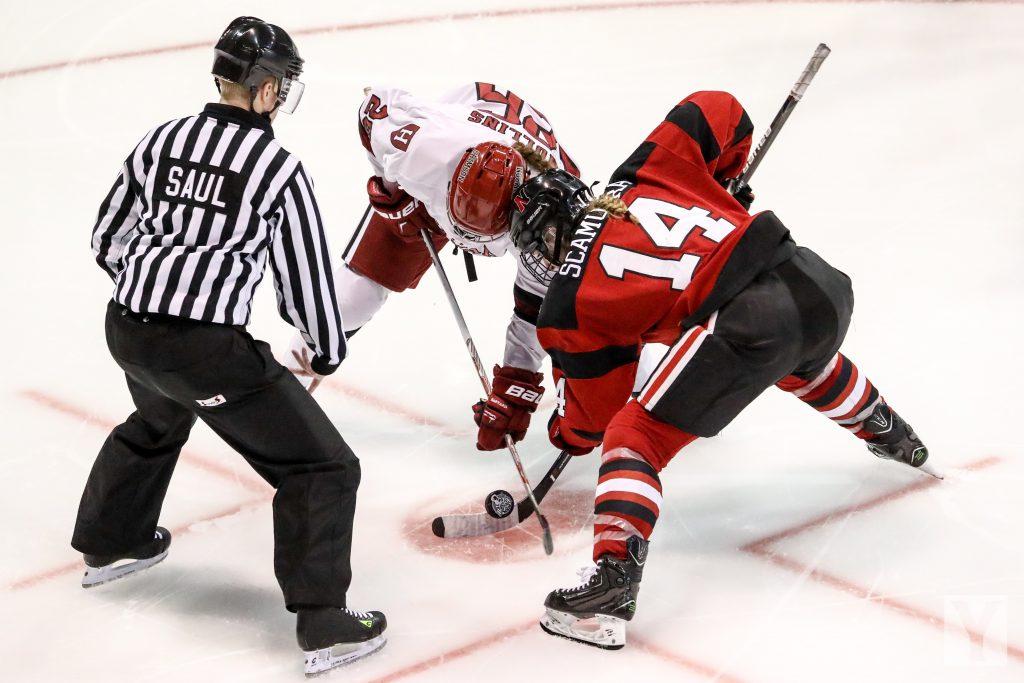 Imagem mostra o momento de uma partida de hóquei no gelo, quando o árbitro solta disco para a disputa entre dois adversários.
