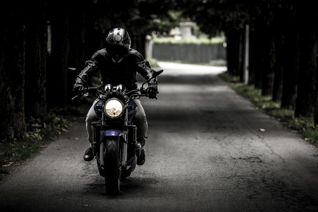 """Imagem mostra um motoqueiro pilotando, com um capacete de visor com insufilm, por uma estrada vazia e """"emoldurada"""" por diversas árvores."""
