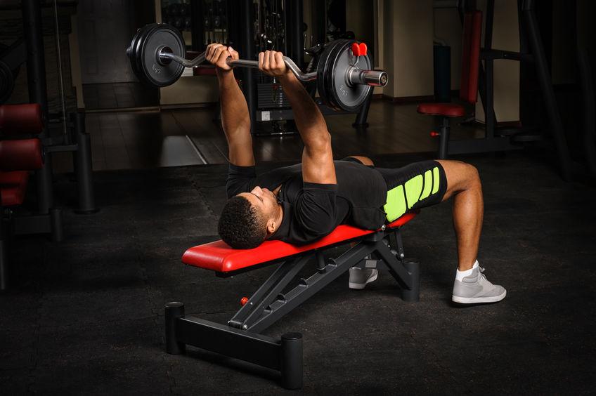 Imagem mostra um homem deitado num pequeno banco supino reclinável, enquanto levanta uma barra ergonômica com duas anilhas de cinco quilos em cada lado.