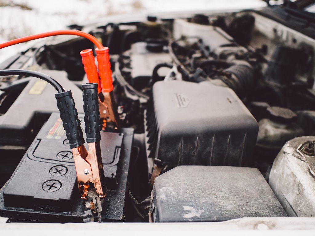 imagem de um capô de carro aberto com fios engatados na bateria