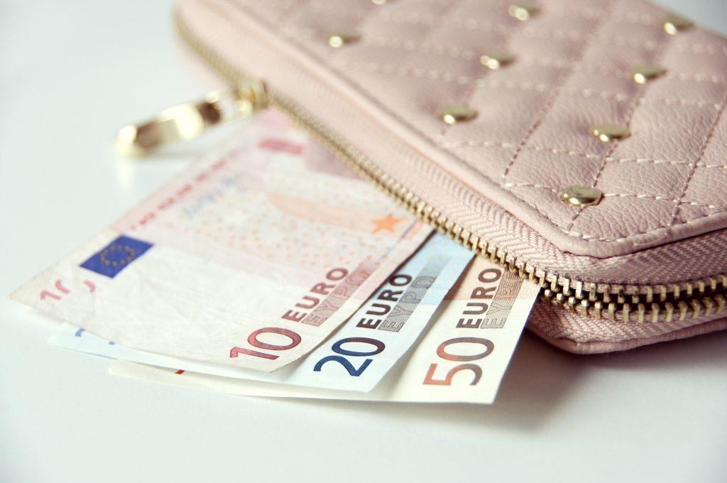 Carteira com três notas de Euro para fora.