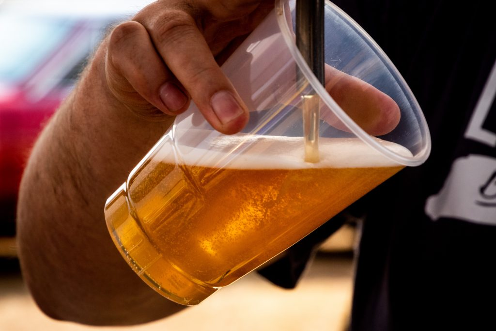 Imagem mostra o close de uma mão segurando um copo de plástico, que é enchido de cerveja pela torneira de uma chopeira.