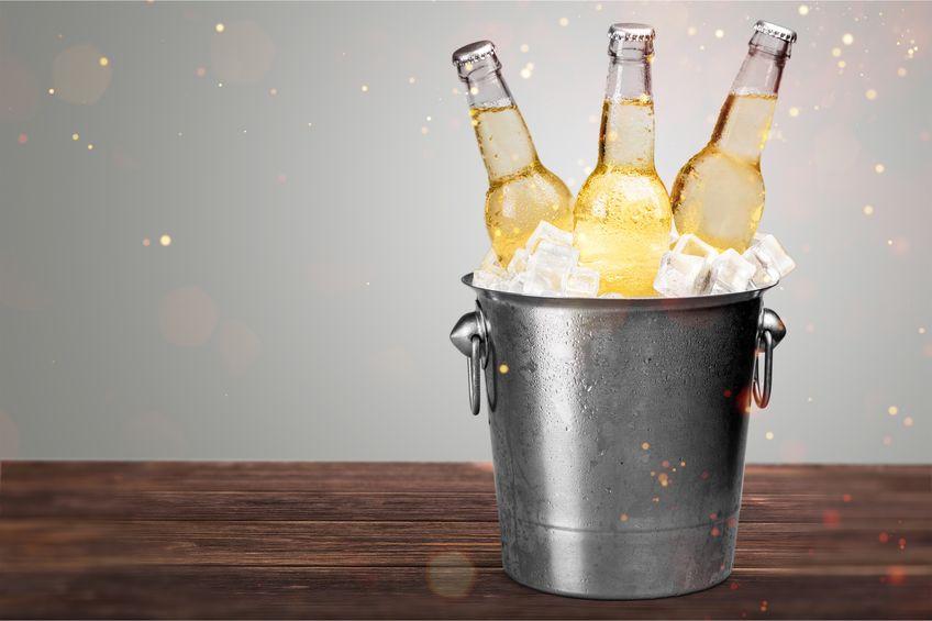 Imagem de cooler de gelo metálico em formato de balde com garrafas de cerveja de marcas variadas sobre areia de praia.