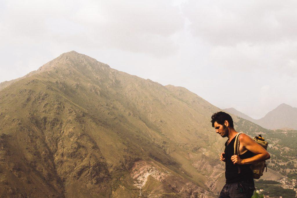 Imagem mostra um homem sobre um terreno alto, com uma mochila nas costas. Ao fundo, uma grande montanha, com neblinas e traços de sua vegetação.