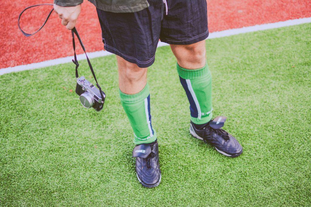 Imagem mostra um corte das pernas de um rapaz uniformizado para jogar futebol. Seus meiões são verdes, do mesmo tom do campo em que pisa.