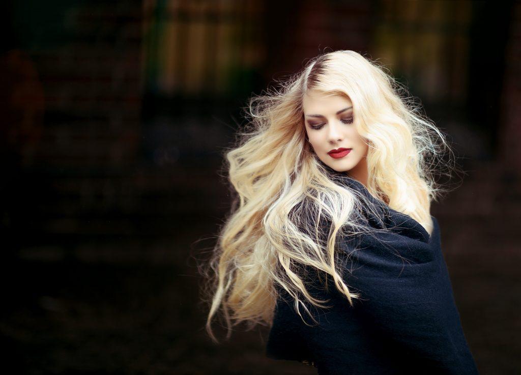 Foto de uma mulher loira com cabelos ao vento.